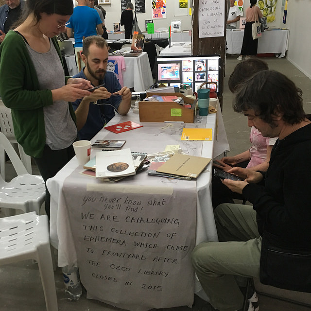 Photograph of people cataloguing works at the Frontyard table at Volume 2017 Book Fair